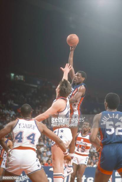 Albert King of the New Jersey Nets shoots over Jeff Ruland of the Washington Bullets during an NBA basketball game circa 1984 at the Capital Centre...
