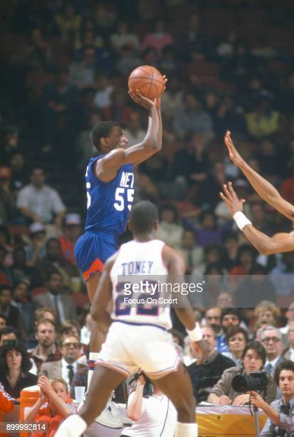 Albert Kings of the New Jersey Nets shoots over Julius Erving of the Philadelphia 76ers during an NBA basketball game circa 1984 at The Spectrum in...