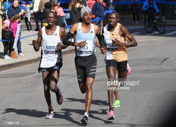 Albert Korir of Kenya Tamara Tola of Ethiopia and Geoffrey Kamworor of Kenya compete in the last minutes of the Men's Division during the 2019 TCS...