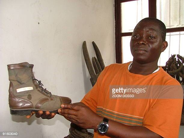 Albert Mackeh the administrator of the National Museum of Liberia holds up the shoe of Prince Johnson the warlord who ordered the killing of former...