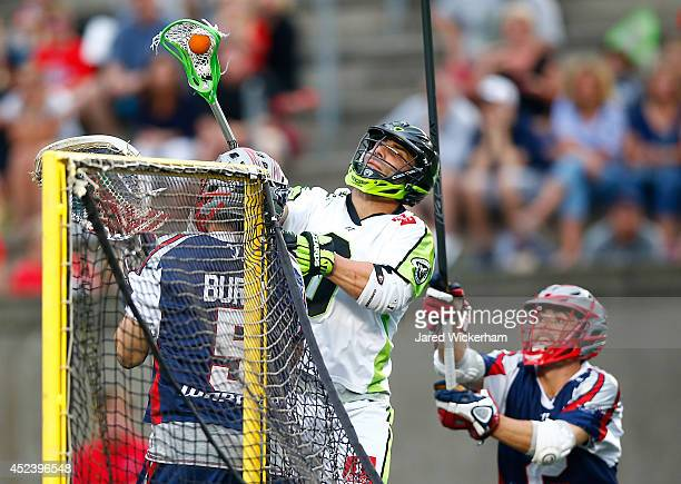 Albert Maione of the New York Lizards takes a shot over Jordan Burke of the Boston Cannons in the second half during the game at Harvard Stadium on...