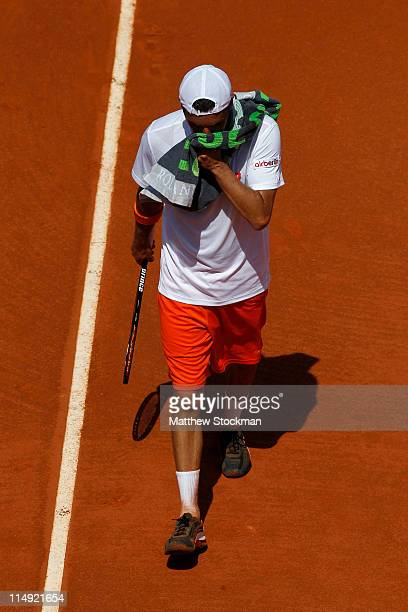 Albert Montanes of Spain wipes his face with a towel during the men's singles round four match between Fabio Fognini of Italy and Albert Montanes of...
