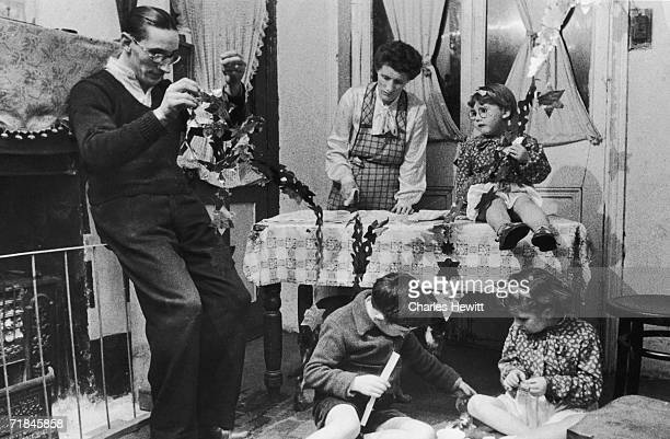 Albert Noakes the glazier helps his family put up the Christmas paper bunting at their house on Christmas Street , south-east London, 21st December...