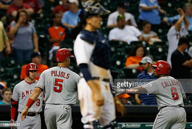 Albert Pujols and Alberto Callaspo of the Los Angeles Angels of Anaheim celebrate a run in the eighth inning as Jason Castro of the Houston Astros...