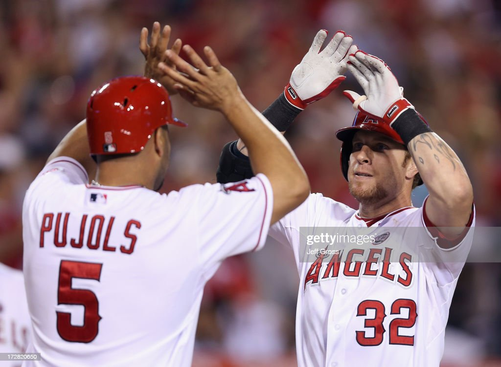 Albert Pujols #5 and Josh Hamilton #32 of the Los Angeles Angels of Anaheim celebrate Hamilton's two-run home run against the St. Louis Cardinals in the ninth inning at Angel Stadium of Anaheim on July 4, 2013 in Anaheim, California. The Angels defeated the Cardinals 6-5.
