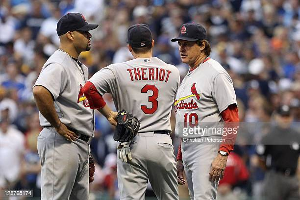 Albert Pujols and Ryan Theriot of the St Louis Cardinals talk with manager Tony LaRussa during a pitching change in the bottom of the seventh inning...
