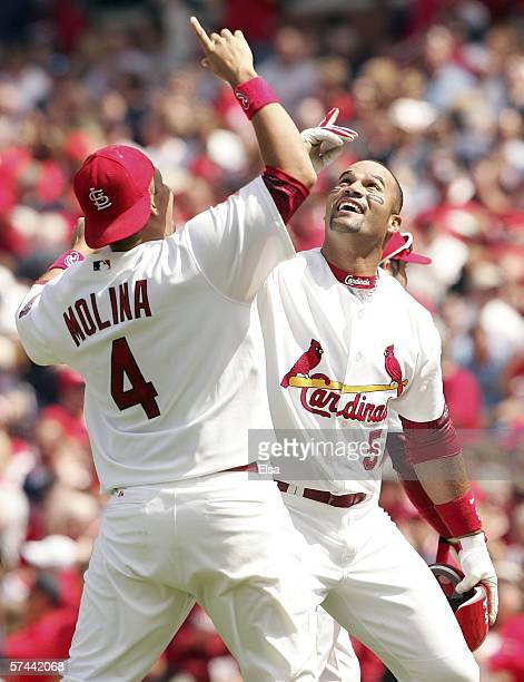 Albert Pujols and Yadier Molina of the St Louis Cardinals celebrate after Pujols drove in the gamewinning run with an RBI single in the bottom of the...