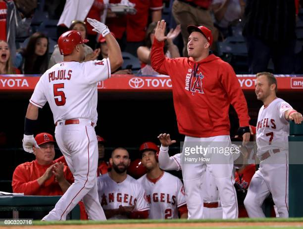 Albert Pujols of the Los Angeles Angels celebrates his 599th homerun for his career with Mike Trout with two men on base to take a 32 lead over the...