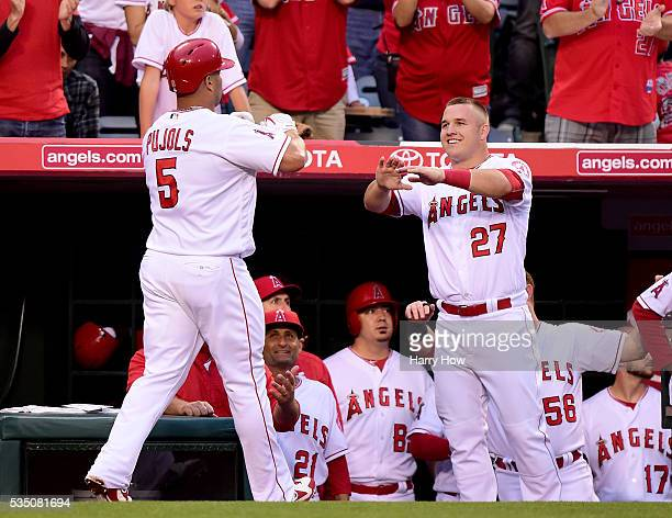 Albert Pujols of the Los Angeles Angels celebrates his solo homerun with Mike Trout to take a 2-1 lead over the Houston Astros during the second...