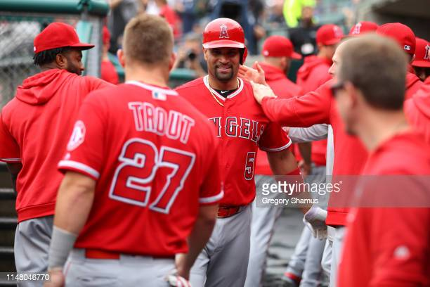 Albert Pujols of the Los Angeles Angels celebrates his third inning solo home run to reach 2000 career RBI's with teammates while playing the Detroit...