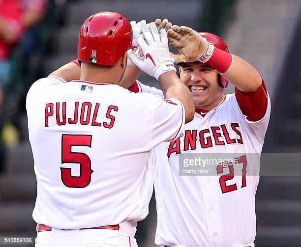 Albert Pujols of the Los Angeles Angels celebrates his two run homerun with Mike Trout to take a 20 lead over the Oakland Athletics during the first...