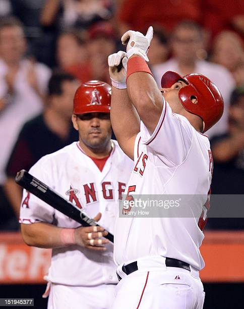 Albert Pujols of the Los Angeles Angels celebrates in front of Kendrys Morales after his homerun to become the first player to hit at least 30...