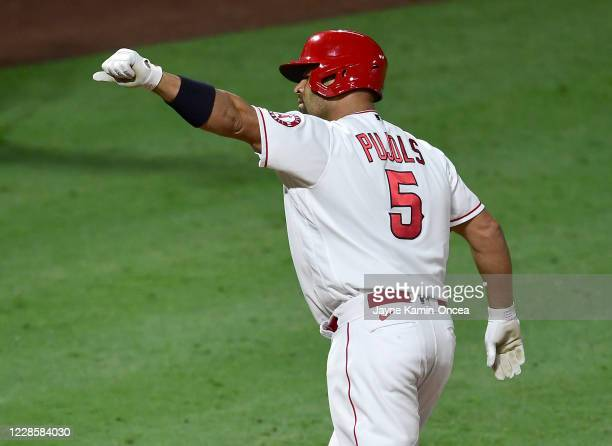 Albert Pujols of the Los Angeles Angels crosses the plate after hitting career home run No. 661 passing Hall of Famer and San Francisco Giants legend...