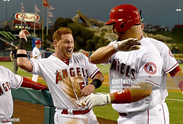 Albert Pujols of the Los Angeles Angels gets a high five from Kole Calhoun of the Los Angeles Angels after a solo home run in the first inning of the...