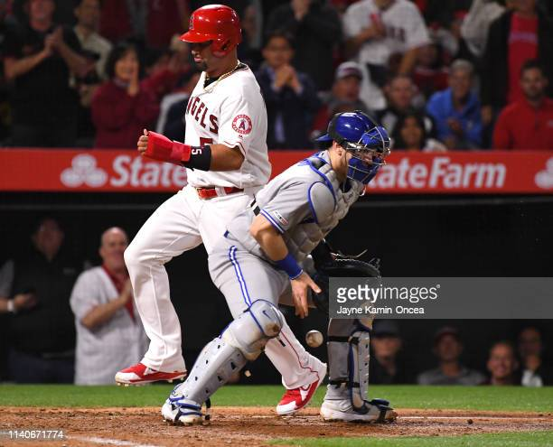 Albert Pujols of the Los Angeles Angels of Anaheim beats the throw to Danny Jansen of the Toronto Blue Jays for a run in the sixth inning of the game...