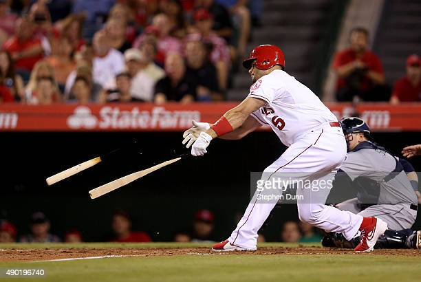 Albert Pujols of the Los Angeles Angels of Anaheim breaks hs bats as he grounds out for the final out of the second inning to leave the bases loaded...