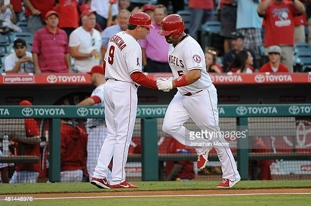 Albert Pujols of the Los Angeles Angels of Anaheim celebrates with Third Base Coach Gary DiSarcina after hitting a home run in the second inning...