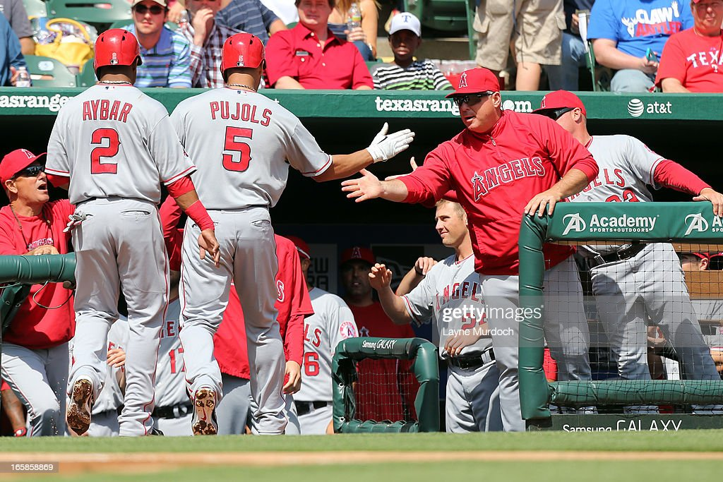 Albert Pujols #5 of the Los Angeles Angels of Anaheim gets a hand shake from manager Mike Scioscia after hitting a two-run homer against Matt Harrison #54 of the Texas Rangers on April 6, 2013 at the Rangers Ballpark in Arlington in Arlington, Texas.