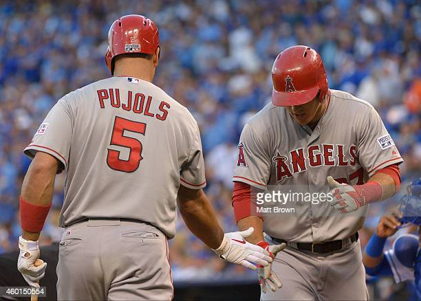 Albert Pujols of the Los Angeles Angels of Anaheim high fives teammate Mike Trout during game 3 of the American League Division Series against the...