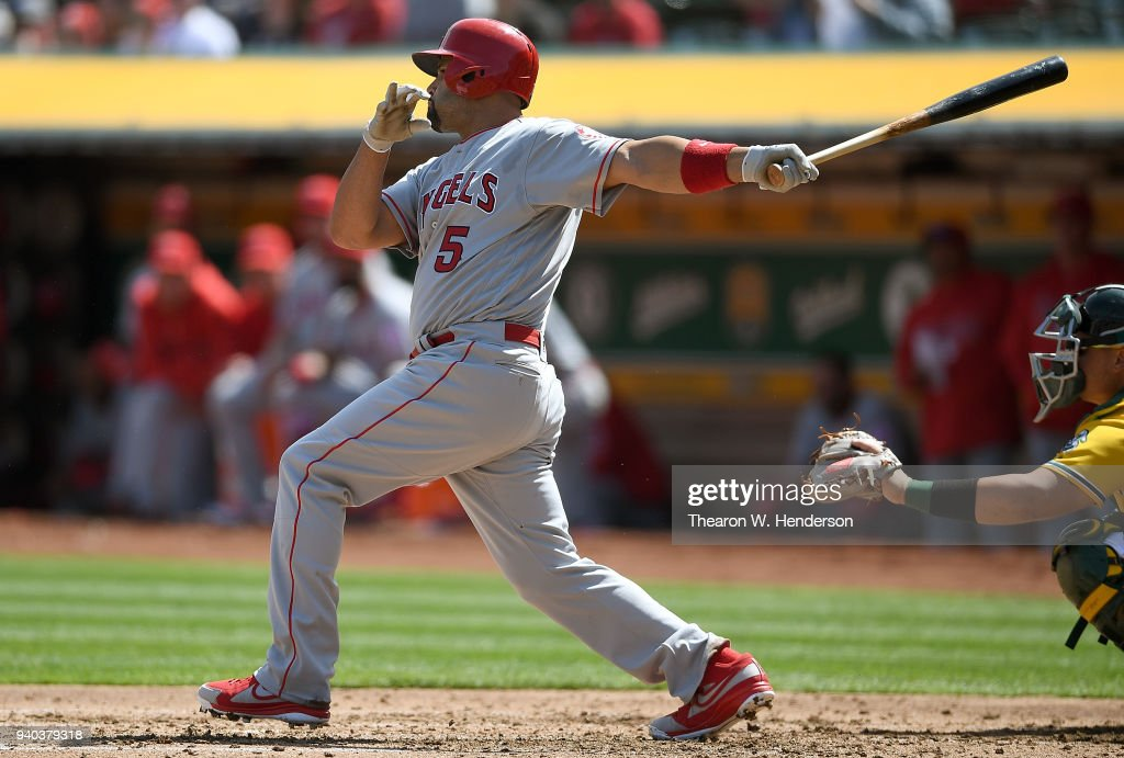 Albert Pujols #5 of the Los Angeles Angels of Anaheim hits an rbi single scoring Mike Trout #27 against the Oakland Athletics in the top of the third of a Major League Baseball game at Oakland Alameda Coliseum on March 31, 2018 in Oakland, California.