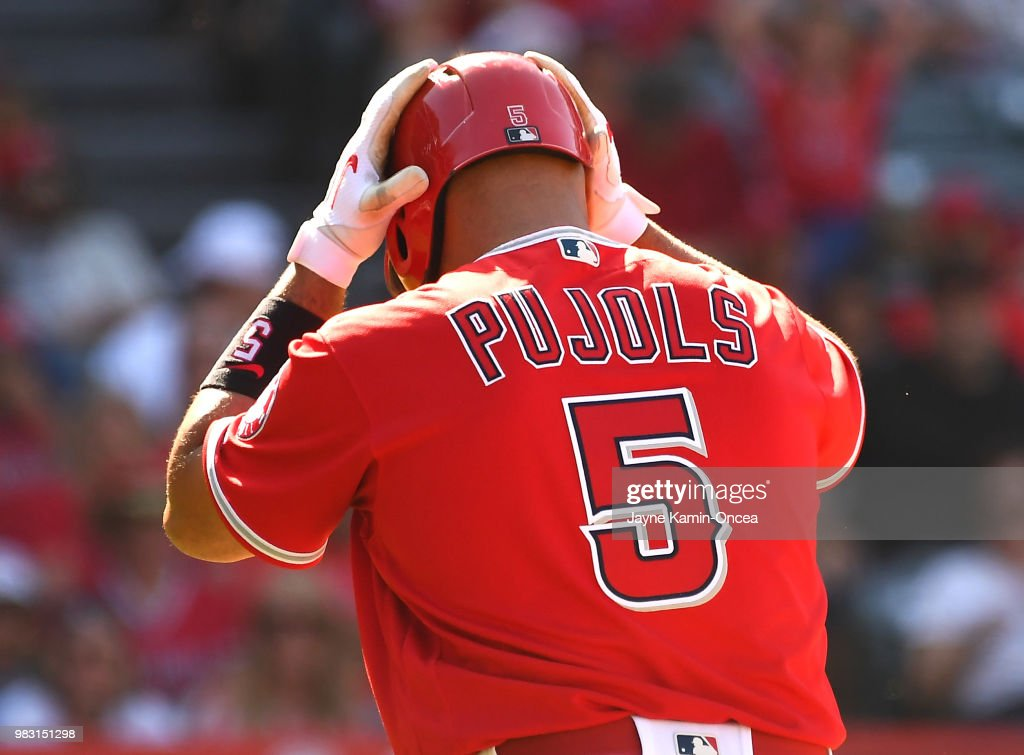 Albert Pujols #5 of the Los Angeles Angels of Anaheim holds his head as he walks back to the dugout after popping out to Devon Travis #29 of the Toronto Blue Jays in the tenth inning of the game at Angel Stadium on June 24, 2018 in Anaheim, California.
