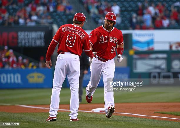 Albert Pujols of the Los Angeles Angels of Anaheim is congratulated by third base coach Gary DiSarcina after Pujols hit a tworun home run in the...