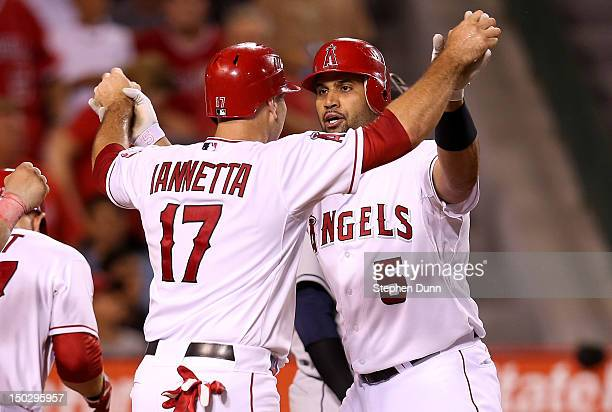 Albert Pujols of the Los Angeles Angels of Anaheim is greeted by Chris Iannetta after both score on Pujols' three run home run in the fourth inning...
