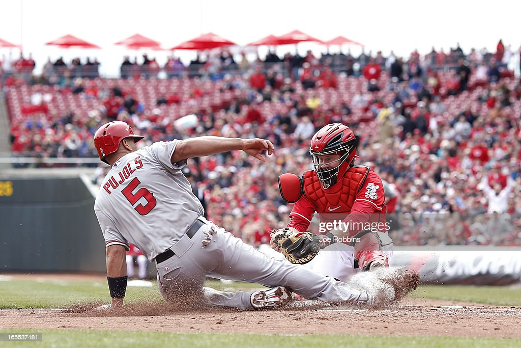 Albert Pujols #5 of the Los Angeles Angels of Anaheim slides into home ahead of the tag by Ryan Hanigan #29 of the Cincinnati Reds during the third inning of the game at Great American Ball Park on April 4, 2013 in Cincinnati, Ohio.