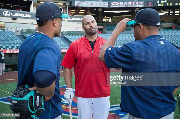Albert Pujols of the Los Angeles Angels of Anaheim talks to Robinson Cano and Joel Peralta of the Seattle Mariners during batting practice before the...