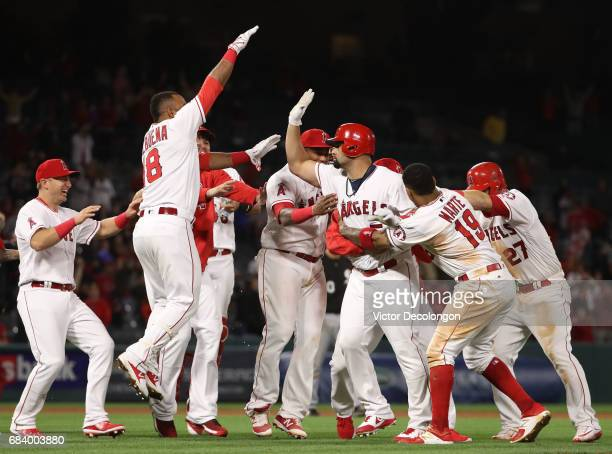 Albert Pujols of the Los Angeles Angels of Anaheim third from right is mobbed by his teammates after Pujols hit the gamewinning run in the 11th...