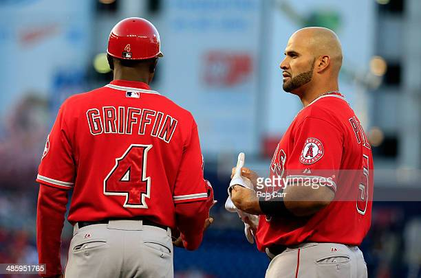Albert Pujols of the Los Angeles Angels talks with first base coach Alfredo Griffin after grounding out for the third out of the first inning against...