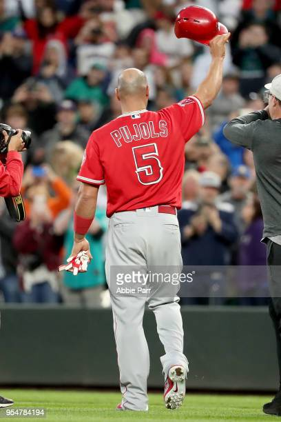Albert Pujols of the Los Angeles Angels tips his helmet to the crowd after hitting a single in the fifth inning against the Seattle Mariners to reach...