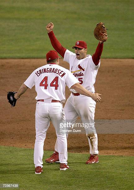 Albert Pujols of the St. Louis Cardinals celebrates with teammates Jason Isringhausen after defeating the Houston Astros 5-2 in game seven of the...