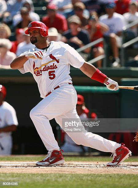 Albert Pujols of the St Louis Cardinals follows through on a single against the Florida Marlins during a Spring Training game at Roger Dean Stadium...