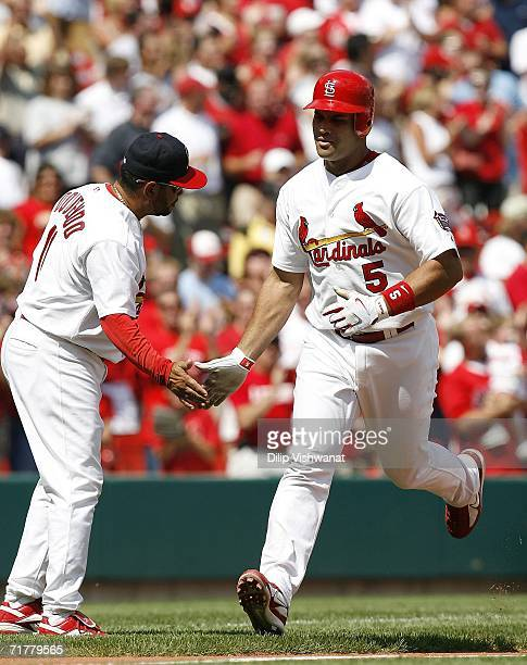 Albert Pujols of the St Louis Cardinals is congratulated by third base coach Jose Oquendo after hitting his second of three home runs against the...