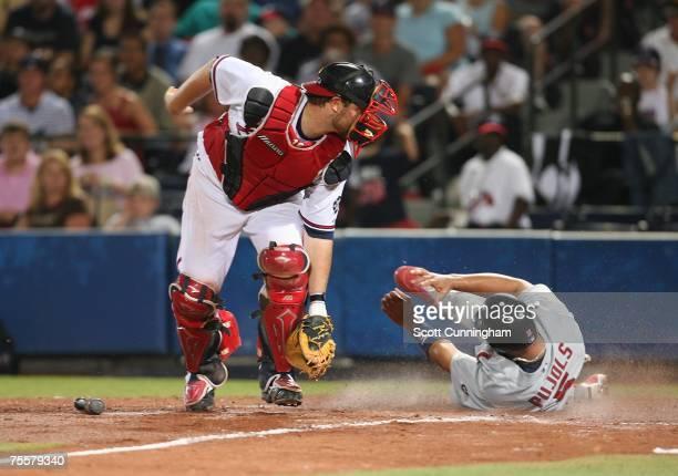 Albert Pujols of the St Louis Cardinals scores against Brian McCann of the Atlanta Braves at Turner Field on July 20 2007 in Atlanta Georgia The...