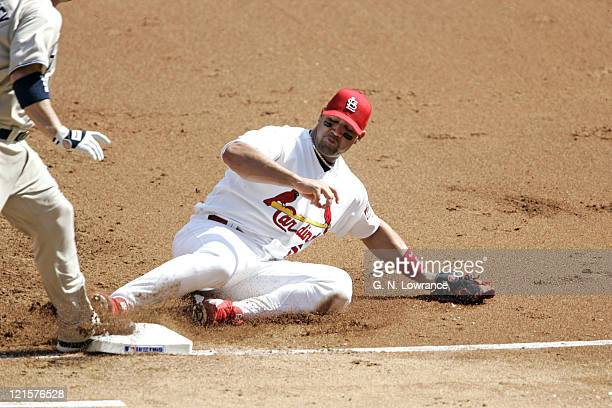 Albert Pujols of the St Louis Cardinals slides into first base against the San Diego Padres during Game 1 of the National League Divisional Playoffs...
