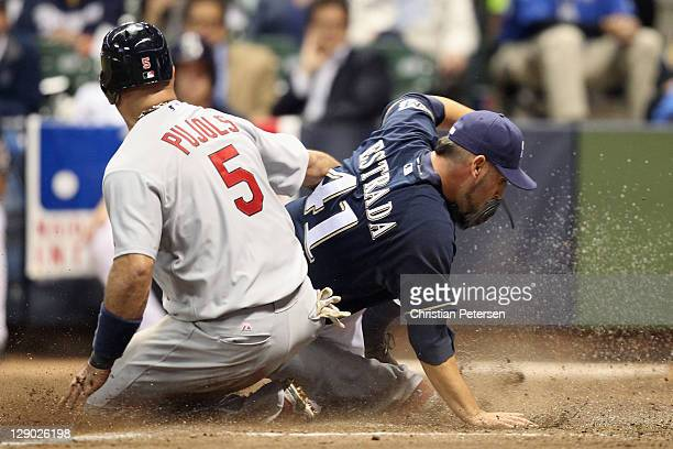Albert Pujols of the St. Louis Cardinals slides safely into home plate against Marco Estrada of the Milwaukee Brewers on a wild pitch by Estrada in...