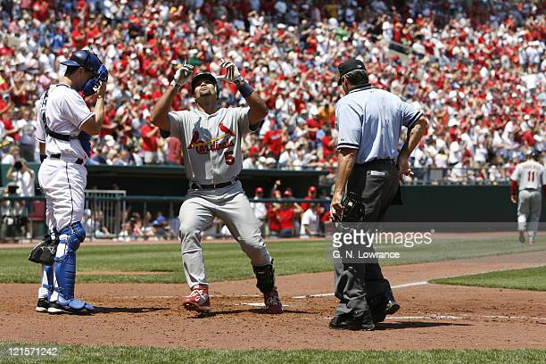Albert Pujols points to the sky after connecting on his 22nd home run of the season during action between the St Louis Cardinals and Kansas City...