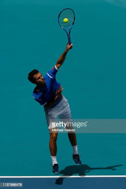 Albert Ramos Vinolas of Spain serves to John Isner of the United States during Day 7 of the Miami Open Presented by Itau at Hard Rock Stadium on...