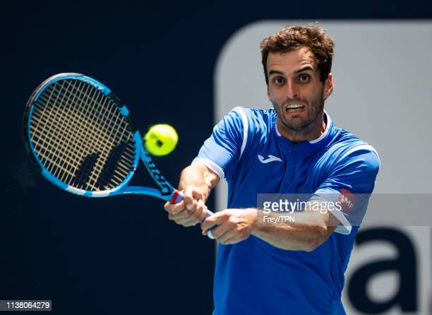 Albert RamosVinolas of Spain hits a backhand against Novak Djokovic of Serbia in the third round of the men's singles in the Miami Open at the Hard...