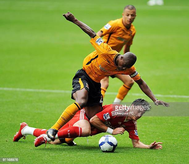 Albert Riera of Liverpool is brought down by George Boateng captain of Hull City during the Barclays Premier League match between Liverpool and Hull...