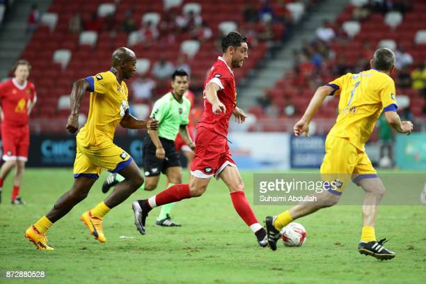 Albert Riera of Liverpool Masters dribbles Luis Boa Morte of Arsenal Masters during the Battle of the Masters at National Stadium on November 11,...