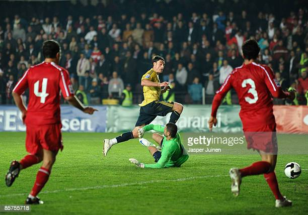 Albert Riera of Spain jumps over goalkeeper Volkan Demirel of Turkey scoring the winning goal during the FIFA2010 World Cup Qualifier match between...
