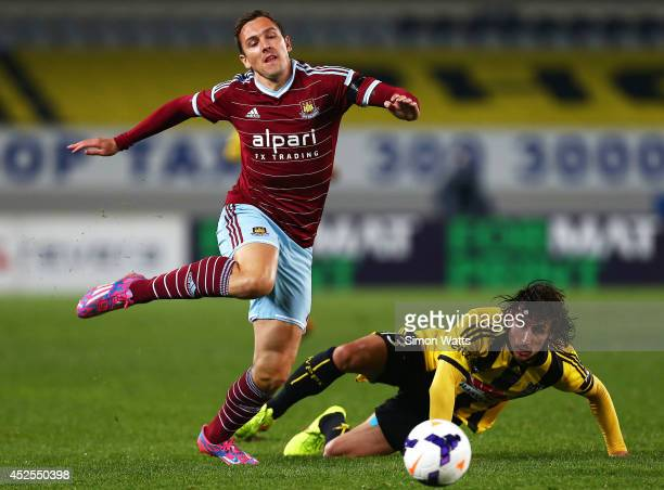 Albert Riera of the Phoenix tackles Stewart Downing of West Ham West Ham United during a football match between the Wellington Phoenix and West Ham...