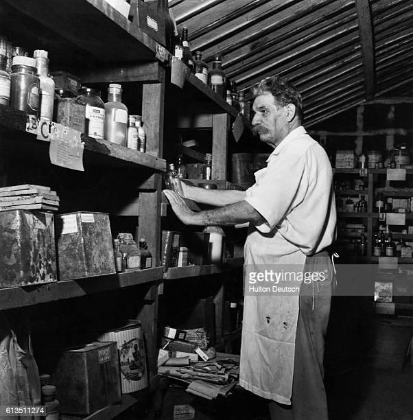 Albert Schweitzer looks over shelves of medicines and supplies