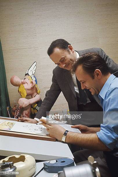 Albert UDERZO home in Neuilly-sur-Seine: the artist sitting at his drawing board, a cigarette in hand, reading a document with his accomplice Rene...