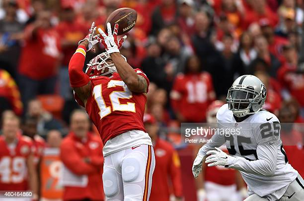 Albert Wilson of the Kansas City Chiefs completes a pass as D.J. Hayden of the Oakland Raiders defends in the first half at Arrowhead Stadium on...