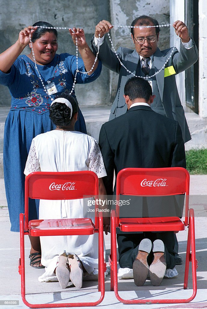 Alberta Contreras de Martinez, top left, and Gerardo Martinez, top right, symbolically lasso their daughter Erica Guadalupe Valadez Contreras to Ivan Acosta Nogami during a wedding ceremony at a prison October 2, 2000 in Ciudad Juarez, Mexico. 5 current and former inmates were married during the same ceremony.