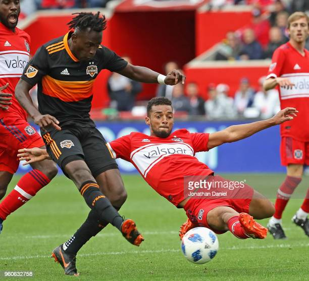 Alberth Elis of the Houston Dynamo fires a shot for a goal past the diving Johan Kappelhof of the Chicago Fire at Toyota Park on May 20 2018 in...